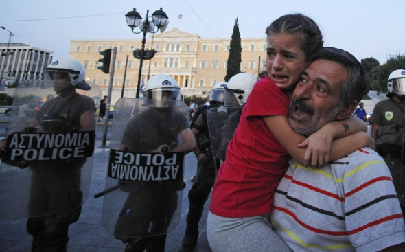 A man and his daughter skirt a protest in front of the Greek Parliament in Athens on Sept. 25. For Greeks, their summer of discontent may have changed seasons but the rallies and protests continue. The nation's economy is buffeted by staggering debts, with the government unable to meet its obligations without help from the European Union and International Monetary Fund. To receive that help, the government must reduce its generous benefits for workers and retirees. In this protest, police used tear gas to disperse about 3,000 protesters who were denouncing the austerity measures. (Kostas Tsironis/Associated Press) #